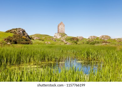 Smailholm Tower.  The view across a mill pond towards Smailholm Tower in the Scottish Borders.  The tower was built in the 1400's as protection from border raiders and the elements.