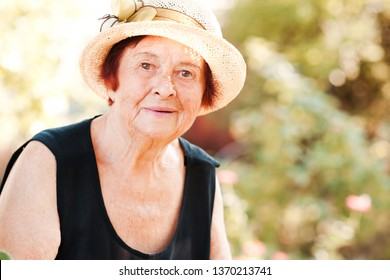Smailing mature woman 70-80 year old wearing straw hat in garden. Looking at camera. Summer season.