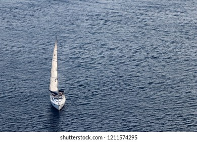 Smaill single masted yacht sails the Aegean sea, near Santorini island, Greece, August 2018, aerial view.