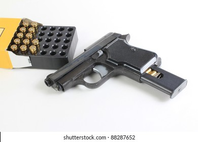 Small .25 caliber hand gun and open box of cartridges to indicate a weapon being loaded.
