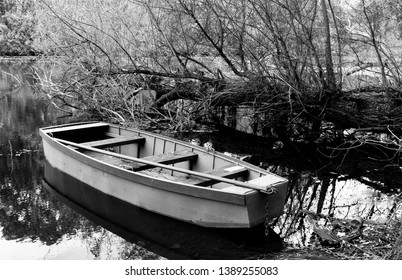 A small abandoned boat floating on smooth water, a river bank surrounded by trees with reflections on the water: an atumn landscape in black and white