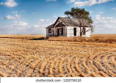 A small abandoned farmhouse stands in the middle of a wheat field in Eastern Washington.