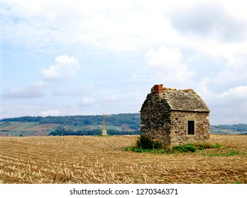 Small abandoned house and cross in middle of harvested field in the Provence, France