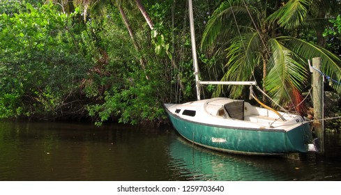 A small abandoned sailboat on a tropical jungle river in South Florida