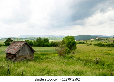 The small abandoned wooden farm located in the green valley surrounded by mountains in Bosnia and Herzegovina