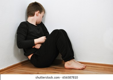 Small abused boy crying in the corner of his home because of domestic violence