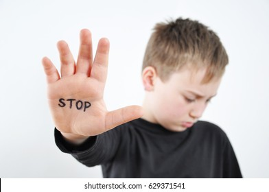 Small abused boy holding his hand with the word 'STOP' written on it. Concept of domestic violence and child abusement.