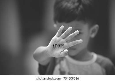 Small abused boy showing his hand with the word 'STOP' written on it. Concept of domestic violence and child abusement. Black and white filter applied to create mood.
