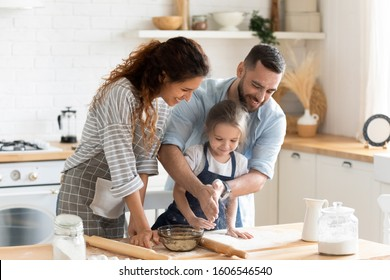 Small adorable kid girl preparing pie with loving caring parents on domestic kitchen, young family enjoy cooking process at home, teaching child, spend weekend together, help, happy parenthood concept