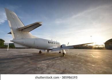 Small aeroplane infront of aircraft hangar during sunrise