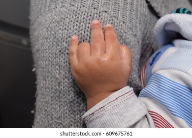 Small African baby boy's hand against the mother's arm