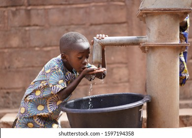Small African Boy Sipping Clean Fresh Water From A Modern Pumping Station