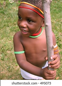 Small African boy wearing colored decorations holding a stick.
