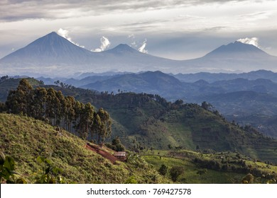 Small African farm cottage set on the side of hill with Volcanoes National Park in Rwanda in the background