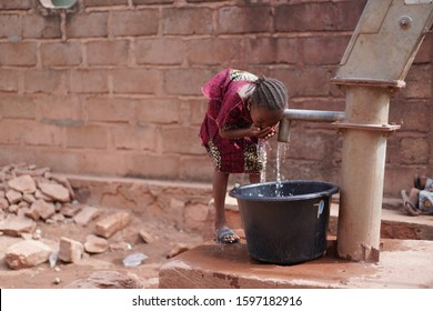 Small African Girl Washing Her Hands At The Village Well