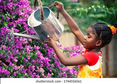 Small African girl watering the flowers in the garden, gardener