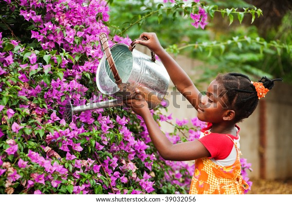 small african girl working in the garden watering the flowers, warm light