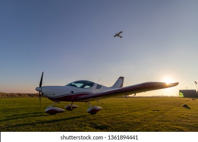 Small aircraft parked by runway with microlight aircraft taking off behind and above