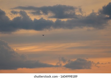 small aircraft silhouette at sunset over lake NH