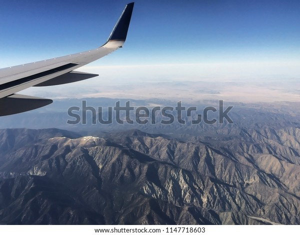 A small airplane fly at The Sierra National Forest located on the western slope of the center of Sierra Nevada in California. The forest is known for its mountain landscapes and natural resources.
