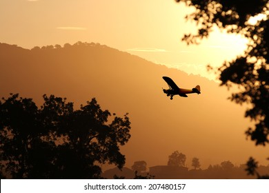 A small airplane flying through the golden yellow mountains preparing to land at sunset.