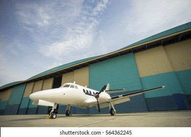 Small airplane and hangar in the blue sunny sky