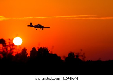 small airplane silhouette against the backdrop of the setting sun