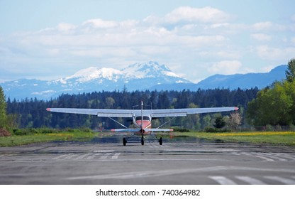 A small airplane takes off from a small airport toward some snow-capped mountains. The photo was taken in Courtenay, British Columbia, but is suitable for a great number of uses.