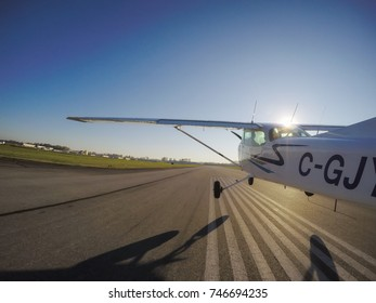 Small airplane is taking off from a runway during a bright sunny day. Taken in Pitt Meadows, Greater Vancouver, British Columbia, Canada. Taken with GoPro