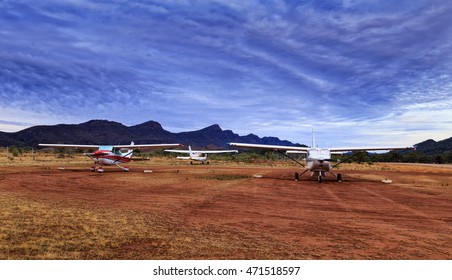 Small  airplanes grounded near Wilpena Pound mountains in Flinders ranges national park shoot at sunrise.