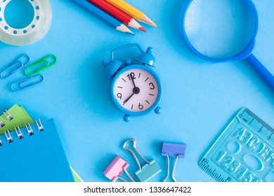 Small alarm clock with school supplies on blue background minimal creative back to school concept.