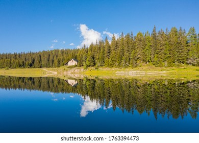 Small alpine chalet immersed in the woods is reflected in the lake. Holidays in Valtellina, Palù lake. Valmalenco