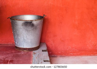 Small aluminum tank on step against red grunge wall