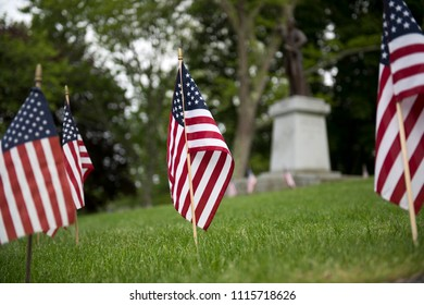 Small American flags are planted throughout a lawn in honor of a patriotic holiday, a memorial statue stands out of focus in the background