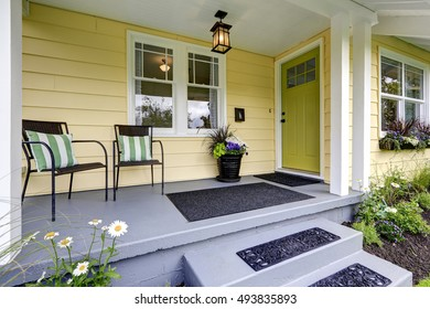 Small American yellow house exterior. Covered porch with stairs. Northwest, USA