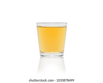 a small amount of whiskey in a glass goblet isolated on a white background