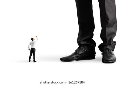 small angry businessman looking up and showing fist to his big boss. isolated on white background