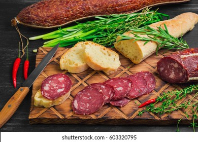 Small antipasto sandwiches from baggetta bread, raw smoked sausage on board, knife. Ingredients for sandwiches with sausage thyme, rosemary, fresh onions, red hot peppers. Dark black wooden background
