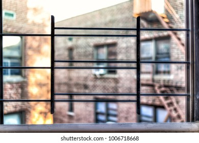 Small apartment window in New York City NYC urban Bronx, Brooklyn brick housing, guard rail, security bars, grunge poverty