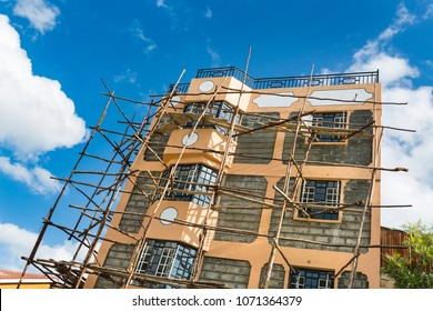 A small appartment building under construction with typical local scaffolding in the village of Tassia in Nairobi, Kenya.