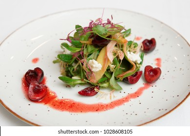 Small appetizer with red berry dressing, cheese and cherries