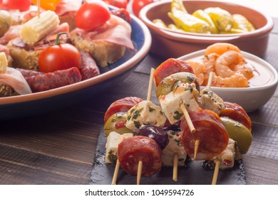Small appetizers on skewer with cheese, olives and sausage. Tapas or antipasto