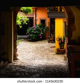 Small archway onto a cobblestone alleyway in a small village in France