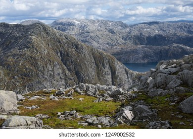 Small area with green grass and moss, surrounded by  bare mountain ridges near the glacier. Blue glacial lake in the next valley. Norway.