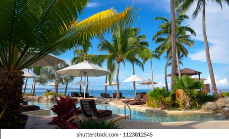 Small artificial waterfall flows into the stunning glassy pool in the middle of luxury beachfront resort being cleaned by the hotel staff. Empty luxury pool and lounge chairs on paradise island resort