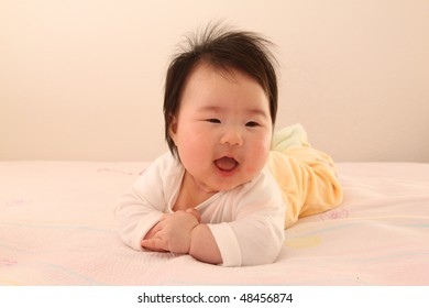Small Asian Baby Infant Crawling on Top of Bed with Smile on Face