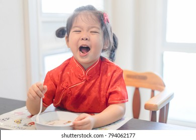 Small asian girl in chinese traditional dress eating granola with milk at home and she have spoon in her mouth in Chinese new year day.