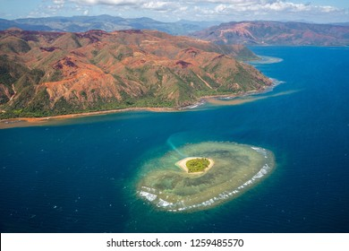 A small atoll islet with heart shaped coral reef off the east coast of Grande Terre island of New Caledonia, French overseas collectivity. Red green mountains hills full of nickel ore near Nakéty.