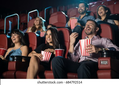 Small audience of people laughing at the movie theater while watching a comedy and having a good time