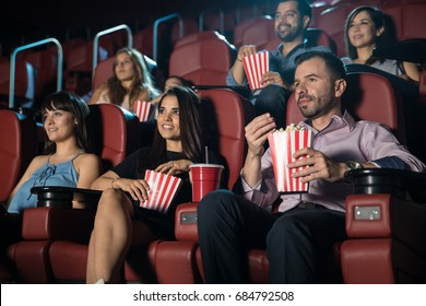 Small audience of young adults watching a movie and eating snacks at the cinema theater